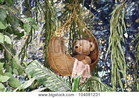 A toy bear in a wire basket hanging in the tree tops.