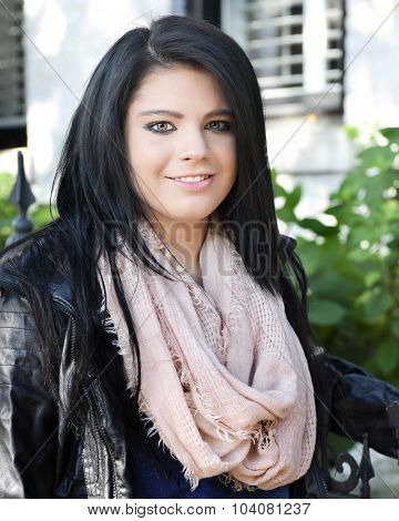Close-up of a beautiful, black-haired teen standing in her scarf and leather jacket by the wrought iron gate of her home.