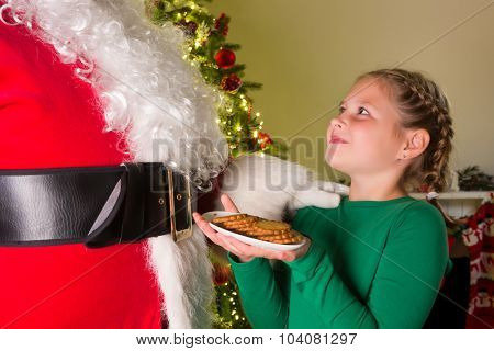 Adorable girl presenting cookies to santa claus