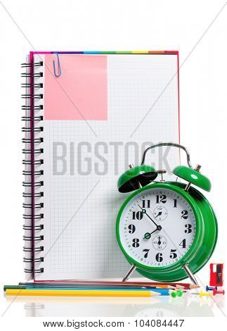 Big green alarm clock with colorful pencils and blank notebook, isolated on white background