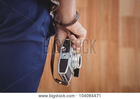 Cropped image of hipster holding camera against wooden wall in office