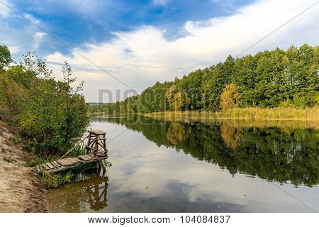 landscape on autumn river with fishing bridge