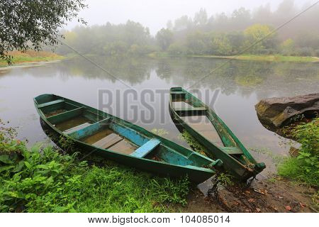 old flooded wooden boats on river at rainy morning time