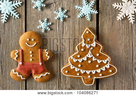 Christmas homemade gingerbread man and tree on wooden table