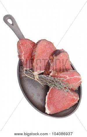 bloody raw beef meat on pan isolated on white background