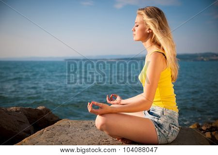 Beautiful Young Blond Woman Meditating On A Beach At Sunrise In Early Summer - Morning Meditation On