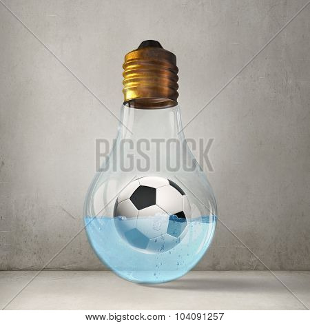 Glass lightbulb with football inside floating in water