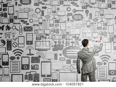 Back view of businessman drawing connection concept on wall
