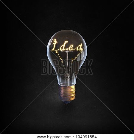 Glowing glass light bulb with word idea inside