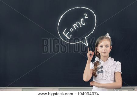 School girl at blackboard pointing at science formula with finger