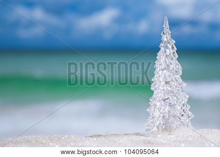 glitter  glass christmas tree  on  beach with seascape background