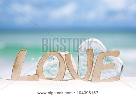 love message and glass hearts on  beach under the sun light with  ocean , beach and seascape, shallow dof