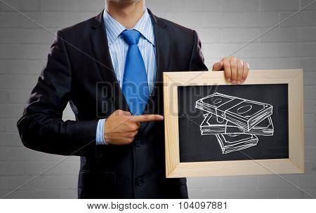 Unrecognizable businessman holding blackboard with drawn money concept