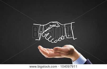 Human hand and sketch of handshake on gray background