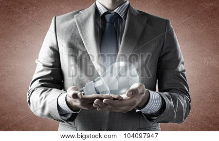 Close up of businessman hands holding glass light bulb