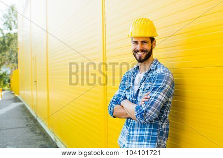Adult Worker With Helmet On Yellow Wall
