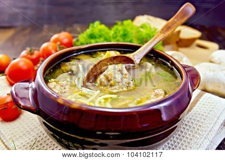 Soup with meatballs and spoon in pottery on board