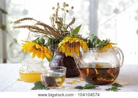 Tea In A Transparent Teapot, Honey And Sunflowers In A Ceramic Vase