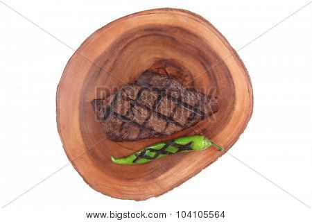 fresh grilled bbq red beef steak on wooden plate with green chili pepper isolated on white background