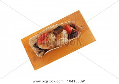 big mexican taco with tomatoes and mushroom on wood plate isolated over white background