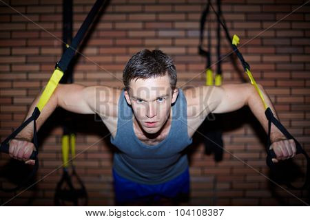 Young man working out in gym on sport equipment