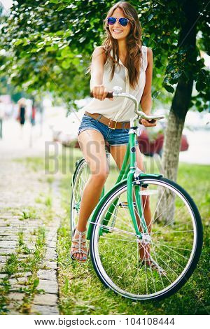 Pretty woman with bicycle spending leisure in park