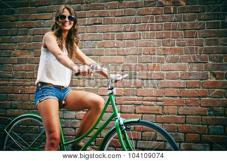 Female bicyclist in eyeglasses standing against brick wall