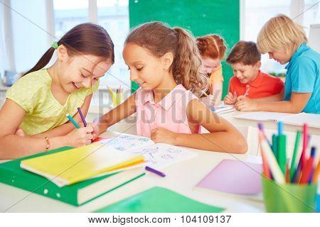Happy schoolgirls drawing together during break
