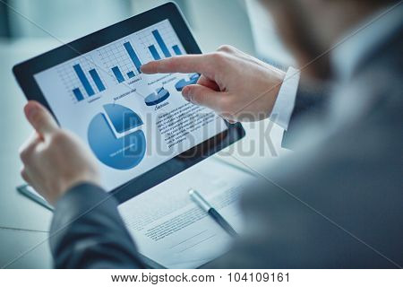 Businessman pointing at electronic document in touchpad during presentation