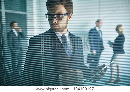 Elegant businessman with digital tablet working in office