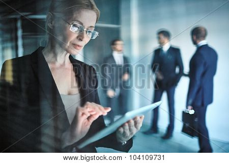 Businesswoman in eyeglasses using digital tablet in working environment