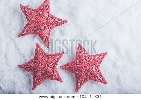Three Beautiful magical vintage red stars on a white snow background. Winter and Christmas concept.