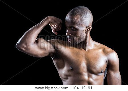 Muscular man looking at bicep while flexing muscles against black background