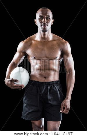 Portrait of shirtless sportsman holding rugby ball against black background