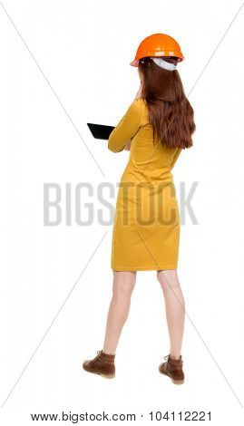 Backview of business woman in construction helmet stands and enjoys tablet or using a mobile phone. Standing young girl. Rear view people collection.  backside view of person.