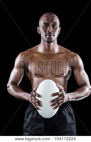 Portrait of shirtless athlete holding rugby ball against black background