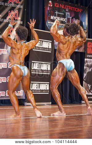 Bodybuilding Duo In Back Double Biceps Pose On Stage