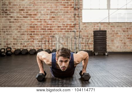 Man doing push up holding dumbbell at the gym
