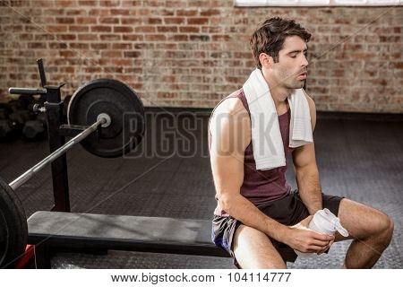 Man holding shaker bottle while sitting at the gym
