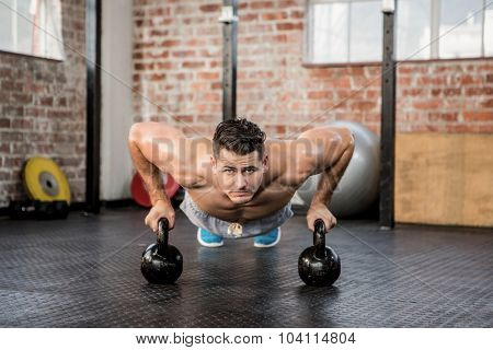 Portrait of man doing push ups with kettlebell at the gym