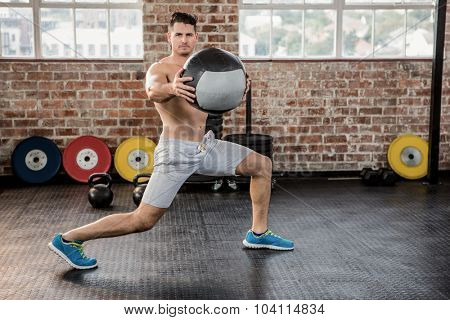 Portrait of muscular man exercising with medicine ball at the gym