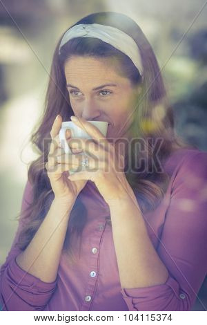 Happy pregnant woman sipping coffee by window at home