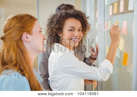 Portrait smiling businesswoman writing on glass as colleagues looking at it during meeting in office