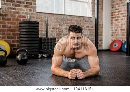 Portrait of a shirtless man doing push ups at the gym