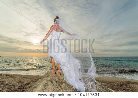 YOung bride by the sea at sunset in Greece