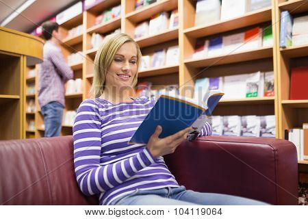 Low angle view of young woman reading book in library