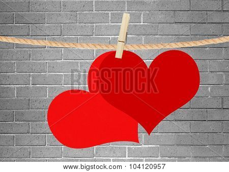 Two Red Hearts Hang On Clothespin Over Grey Brick Wall