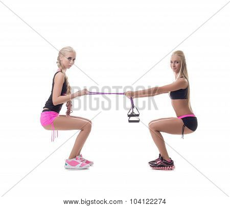 Squats. Two sexy blondes exercising with expander