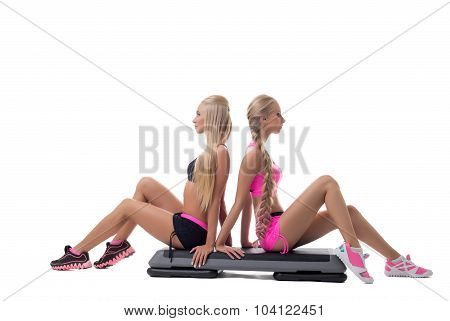 Shaping. Pretty blondes posing sitting on stepper
