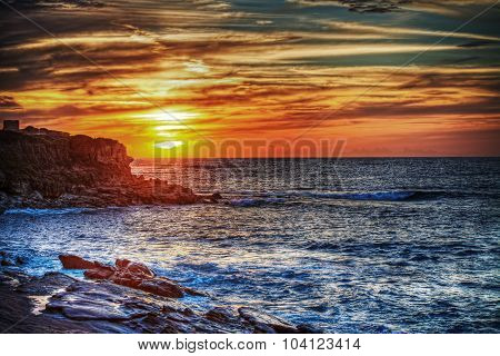 Rocky Shore Under A Colorful Sky In Sardinia